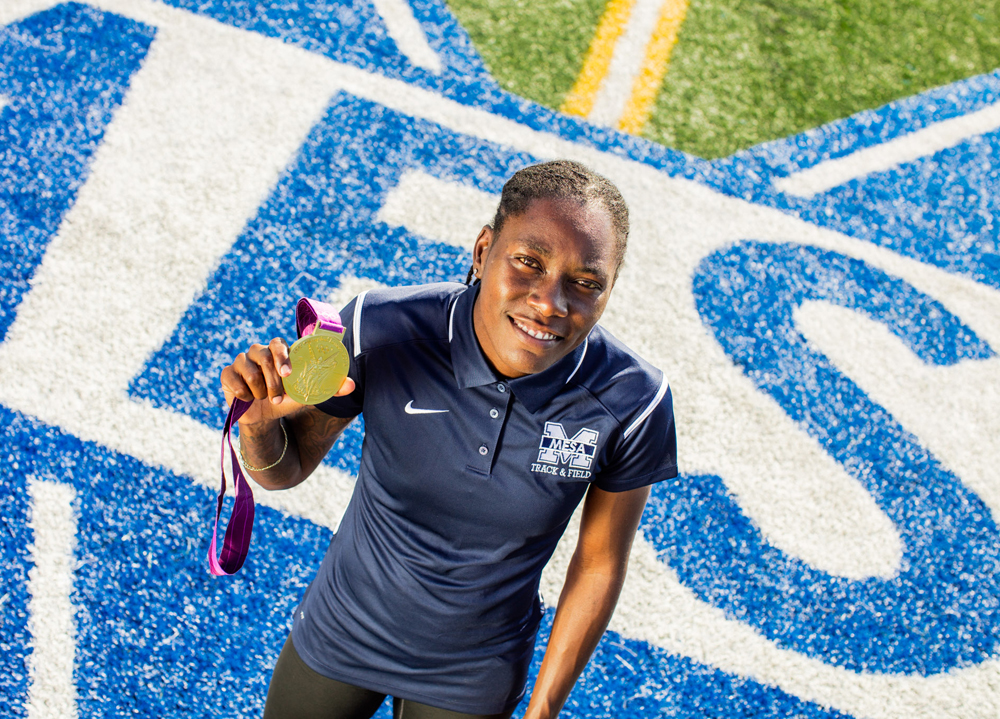 Brittney Reese holds 2012 Long Jump Gold Medal on field at San Diego Mesa College.